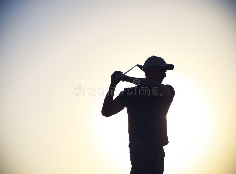 Mannelijke golfspeler bij zonsondergang stock afbeelding