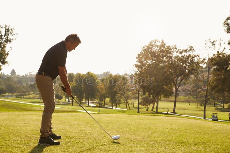 Mannelijke Golfspeler die die T-stuk opstellen op Golfcursus wordt geschoten stock foto's