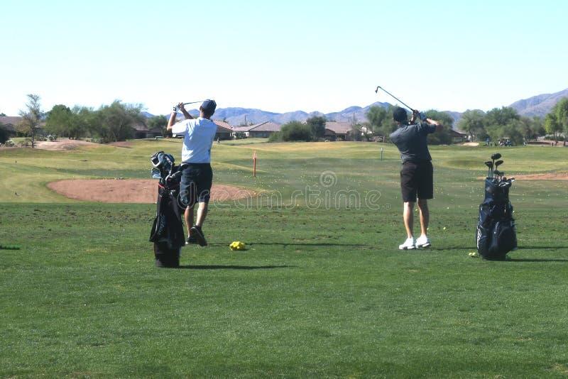 Mannelijke Golfspeler die een golfbal van een achtermening raken royalty-vrije stock afbeelding