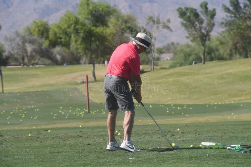 Mannelijke Golfspeler die een golfbal van een achtermening raken royalty-vrije stock foto's