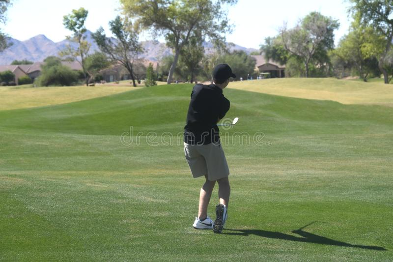 Mannelijke Golfspeler die een golfbal van een achtermening raken stock fotografie