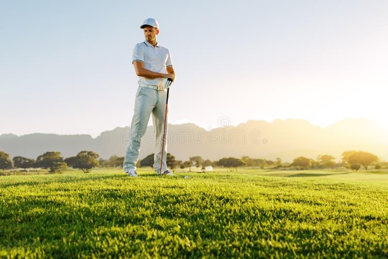 Mannelijke golfspeler met golfclub die op gebied weg kijken stock fotografie