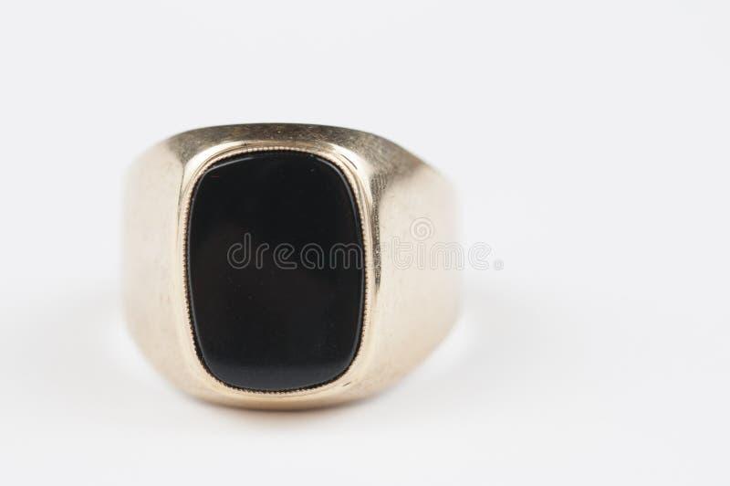 Mannelijke gouden ring met zwarte steen op een witte achtergrond stock foto