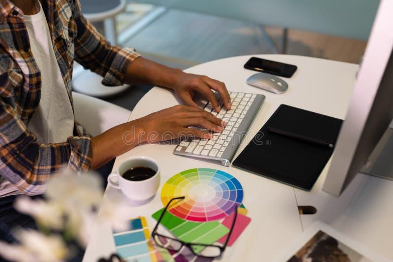 Mannelijke grafische ontwerper die aan computer bij bureau in bureau werken stock foto