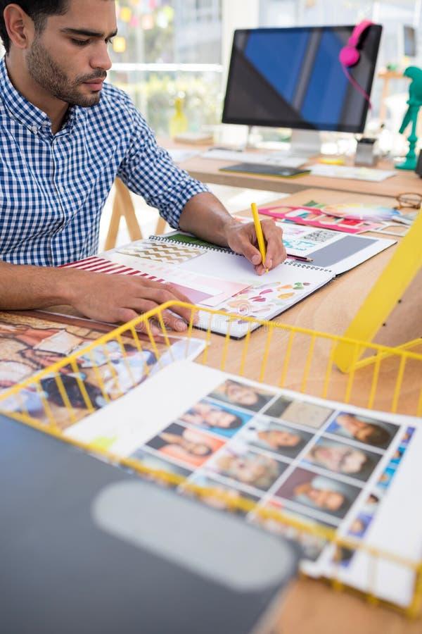 Mannelijke grafische ontwerper die bij bureau werken royalty-vrije stock afbeeldingen