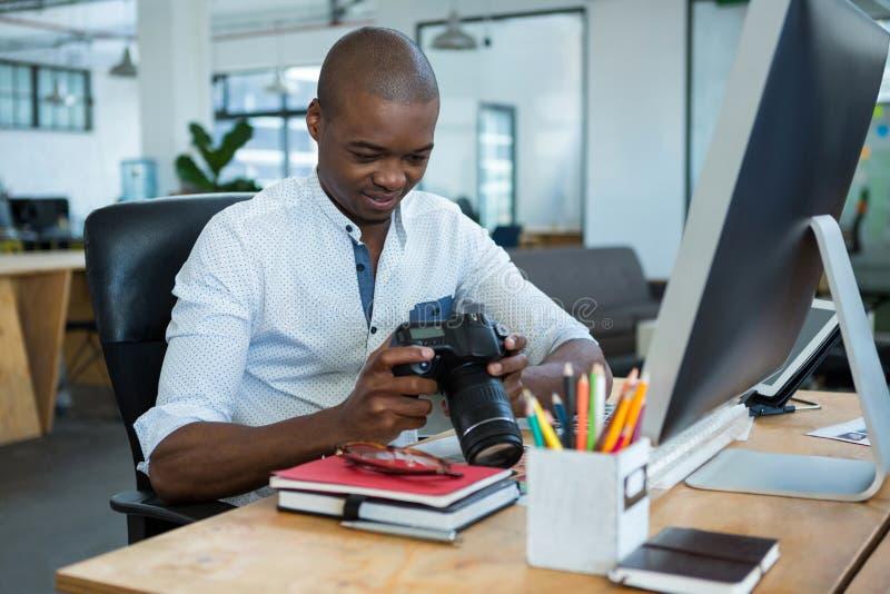 Mannelijke grafische ontwerper die gevangen beelden in zijn digitale camera herzien bij bureau stock afbeelding