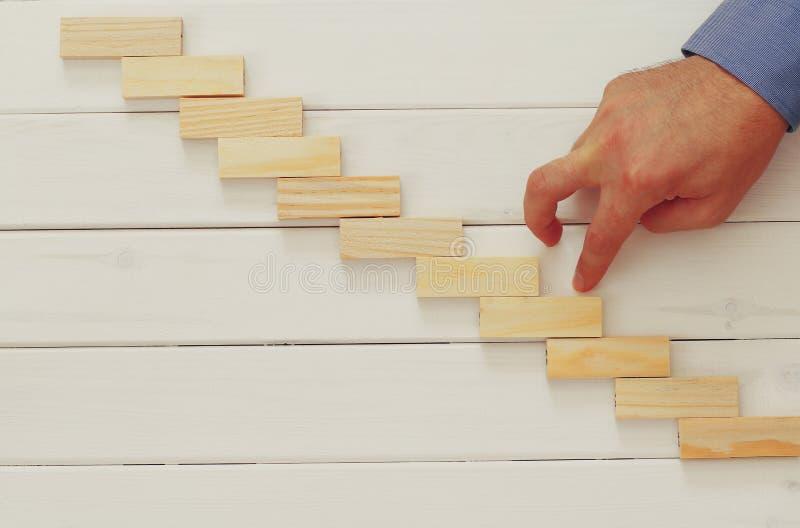 Mannelijke hand de bouwladder van dominobakstenen royalty-vrije stock afbeeldingen