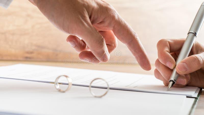 Mannelijke hand die aan een scheidingsdocument richten stock afbeeldingen