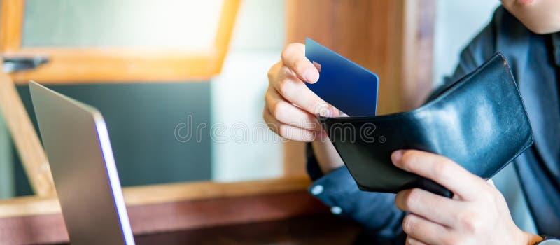 Mannelijke hand die creditcard zetten in zijn portefeuille stock afbeeldingen