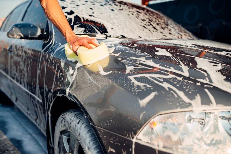 Mannelijke hand die de auto met schuim wrijven, carwash stock foto's