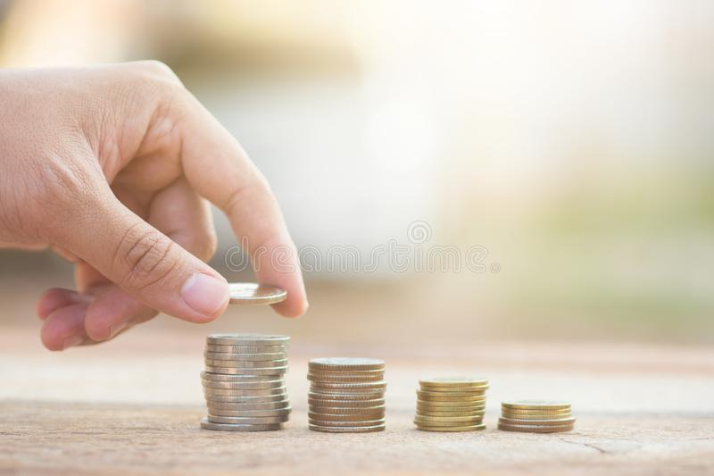 Mannelijke hand die de stapel groeiende zaken zetten van het geldmuntstuk royalty-vrije stock foto