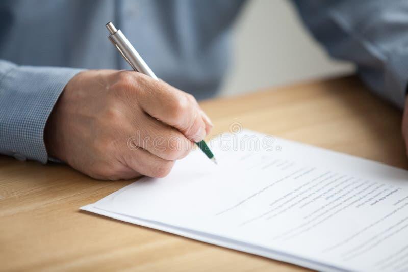 Mannelijke hand die document, hogere mens ondertekenen die handtekening op pape zetten stock foto's