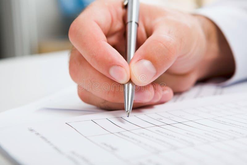 Mannelijke hand die in document schrijft royalty-vrije stock afbeelding