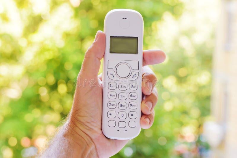 Mannelijke hand die draadloze landline telefoonontvanger in openlucht houden royalty-vrije stock foto's