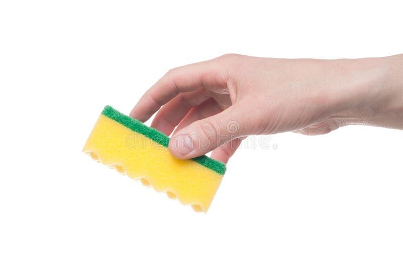 Mannelijke hand die een gele schoonmakende spons houden die op een witte achtergrond wordt geïsoleerd royalty-vrije stock afbeelding