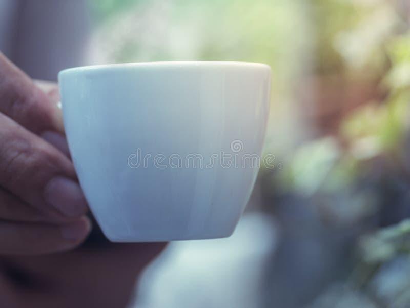 Mannelijke hand die een kleine koffiekop houden royalty-vrije stock foto