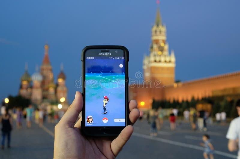 Mannelijke hand die een Samsung-Melkwegsmartphone met het lopen Pok houden stock fotografie
