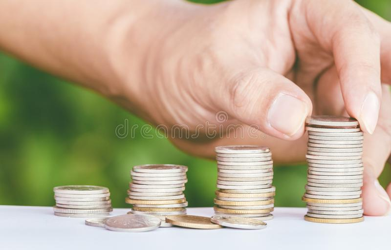 Mannelijke hand die geldmuntstuk zoals stapel groeiende zaken zetten stock foto's
