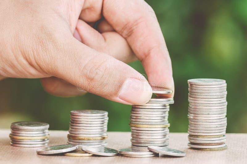 Mannelijke hand die geldmuntstuk zoals stapel groeiende zaken zetten stock fotografie