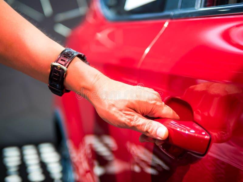 Mannelijke hand die het deurhandvat van rode auto houden stock foto