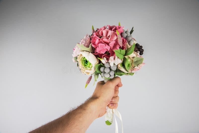 Mannelijke hand die huwelijksboeket geven stock foto