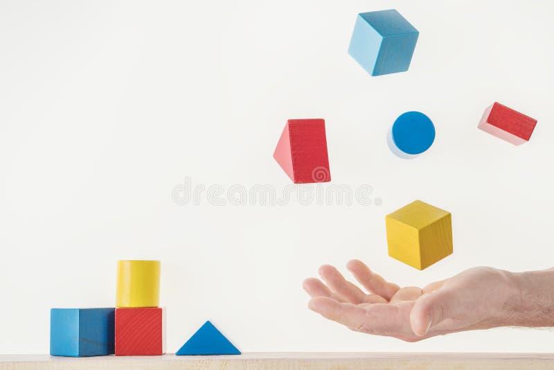 Mannelijke hand die met kleurrijke houten vormen jongleren royalty-vrije stock afbeelding