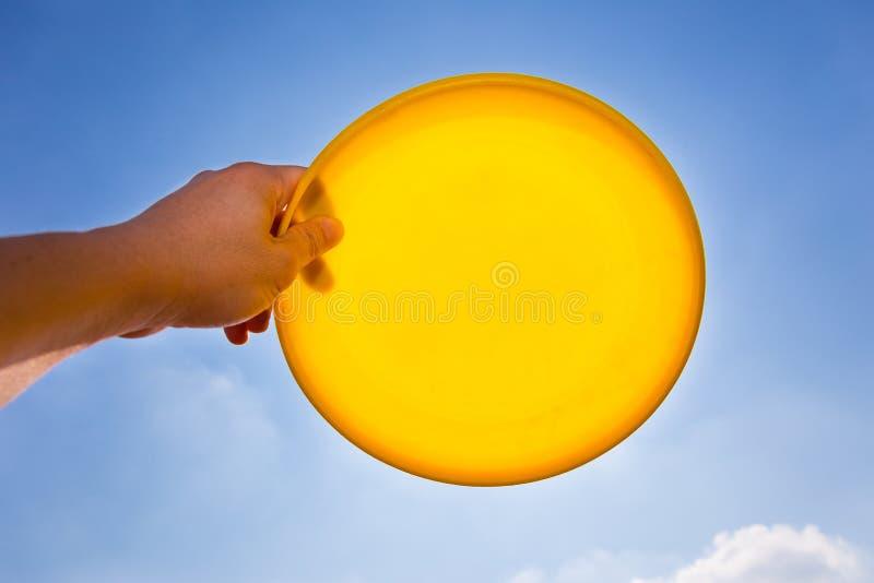 Mannelijke hand die schijf van holdings de gele frisbee vangen tegen blauwe hemel royalty-vrije stock fotografie