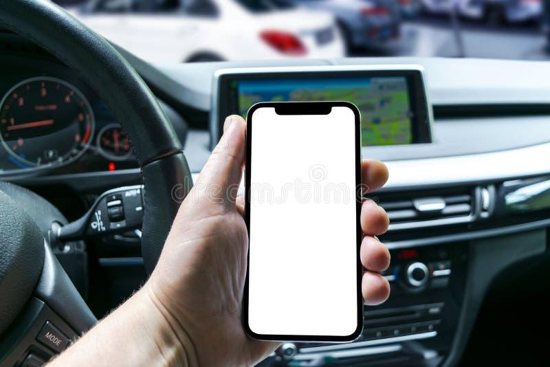 Mannelijke hand die smartphone in auto gebruiken Mens die een auto drijft Smartphone in een autogebruik voor Navigate of GPS Mobi stock foto's