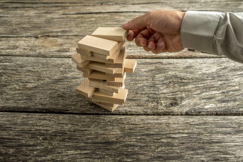 Mannelijke hand die of tot een toren van vele houten blokken leiden bouwen stock afbeeldingen