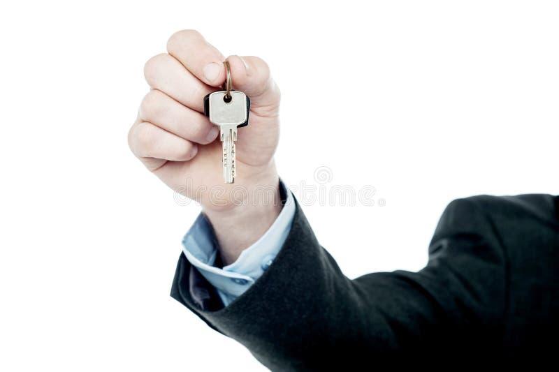 Mannelijke hand die uw die sleutel geven, op wit wordt geïsoleerd stock foto