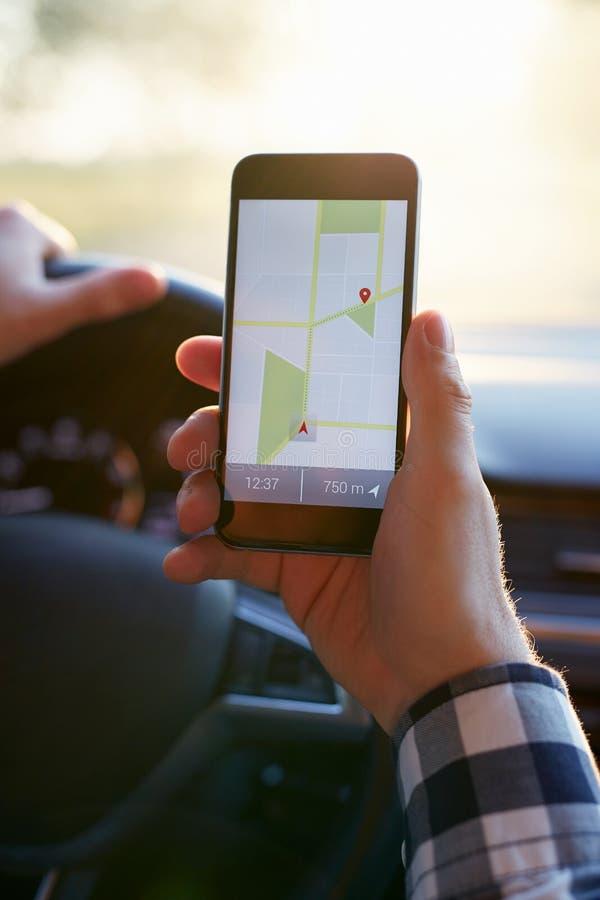 Mannelijke hand die zwarte mobiele telefoon met gps kaart houden royalty-vrije stock fotografie