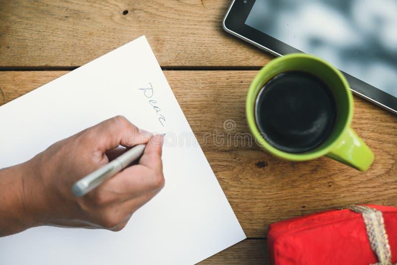 Mannelijke hand het schrijven brief naast rode giftbox en royalty-vrije stock fotografie