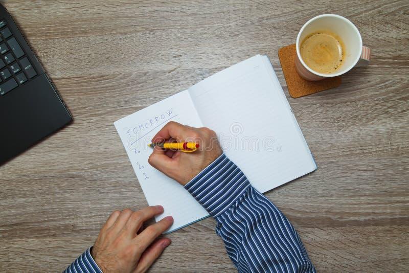 Mannelijke hand het schrijven tekst ` om ` in notitieboekje te doen terwijl aangezien hij koffie drinkt royalty-vrije stock foto