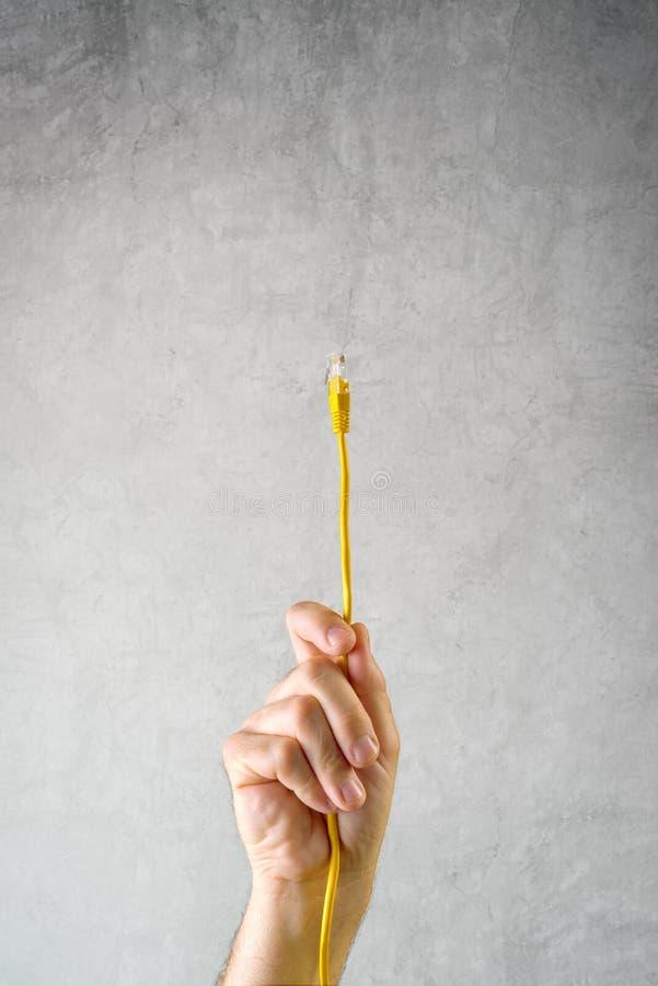 Mannelijke hand met LAN kabel die met netwerk verbinden royalty-vrije stock afbeelding