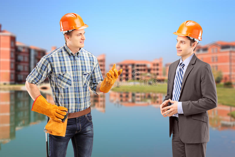 Mannelijke handarbeider die een gesprek met architect, constru hebben stock afbeelding