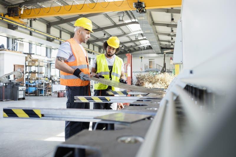 Mannelijke handarbeiders die bladmetaal onderzoeken bij de industrie stock afbeelding