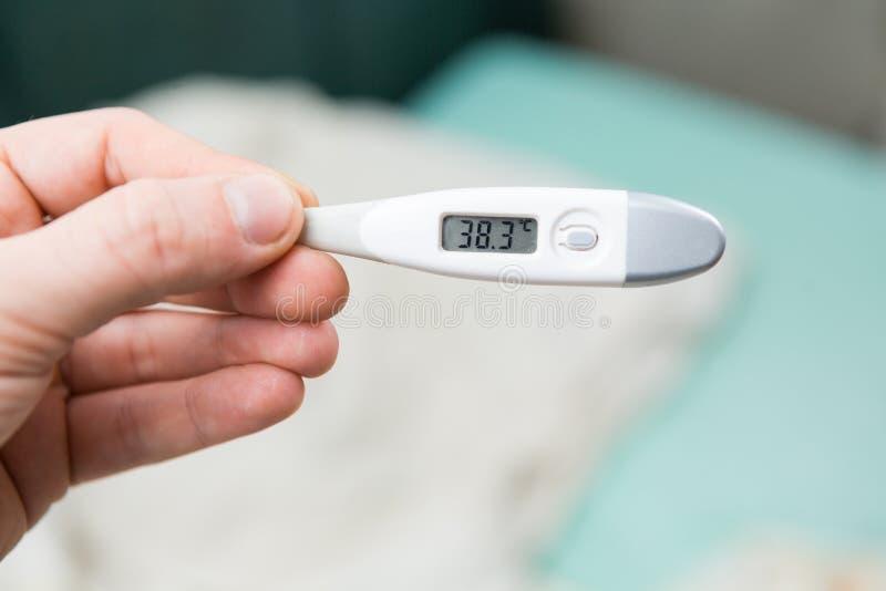 Mannelijke handen die een digitale thermometer houden stock foto