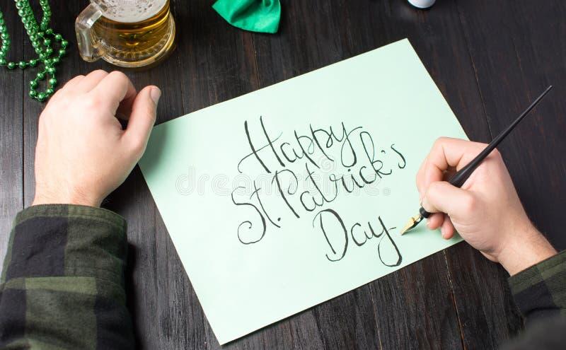 Mannelijke handen die een Gelukkige St Patrick dagkaart schrijven stock foto's