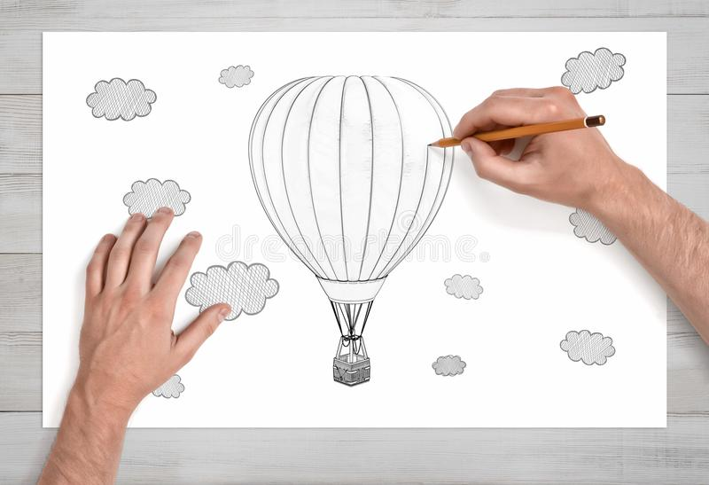 Mannelijke handen die een hete luchtballon onder de wolken met een potlood trekken op een Witboek in dichte mening royalty-vrije stock fotografie