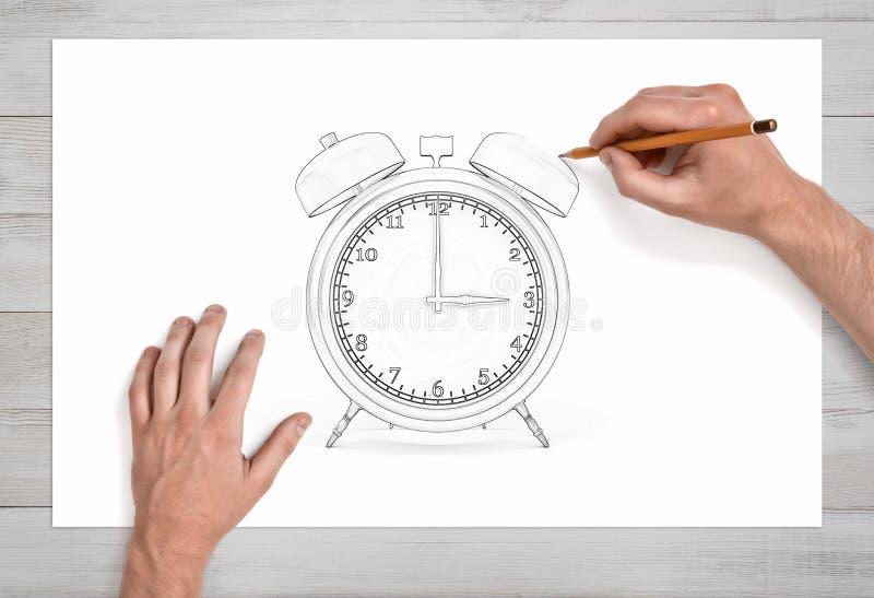 Mannelijke handen die een retro alarmblok met twee klokken trekken die een potlood gebruiken op een Witboek in dichte mening stock afbeeldingen