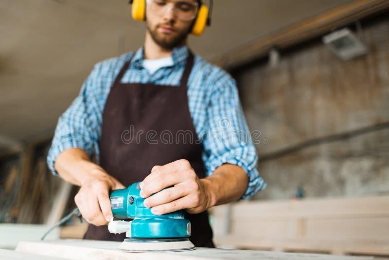 Mannelijke handen die elektrische schuurmachine in werking stellen stock foto