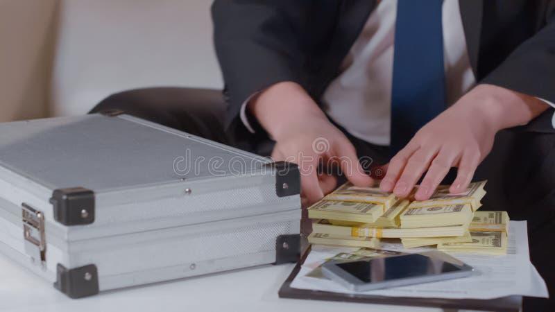 Mannelijke handen die groot geld op lijst, bedrijfsleningsconcept, investeringsclose-up houden stock fotografie