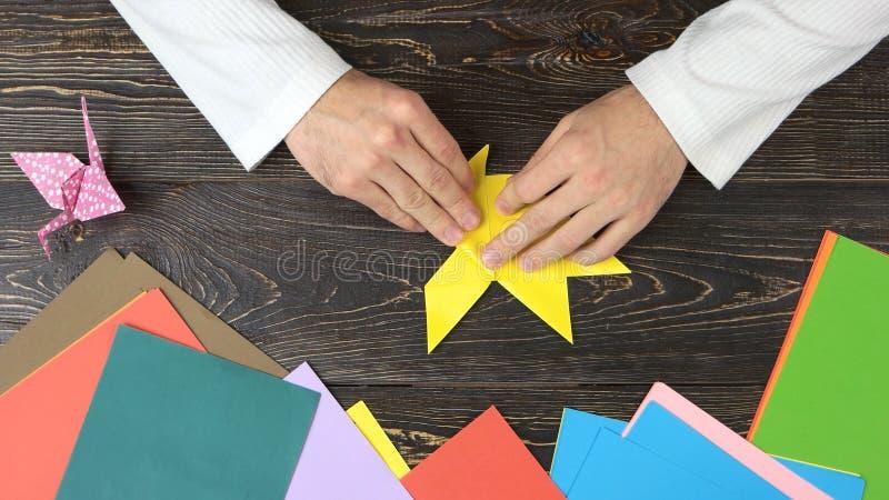 Mannelijke handen die origamivlinder maken royalty-vrije stock afbeelding
