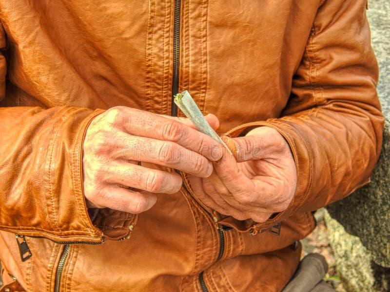 Mannelijke handen die sigaren met tabak rollen Sigaret, sigaar stock foto
