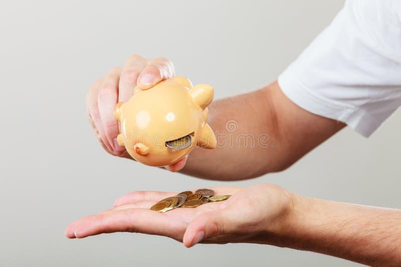 Mannelijke handen met muntstukken en piggybank stock afbeeldingen