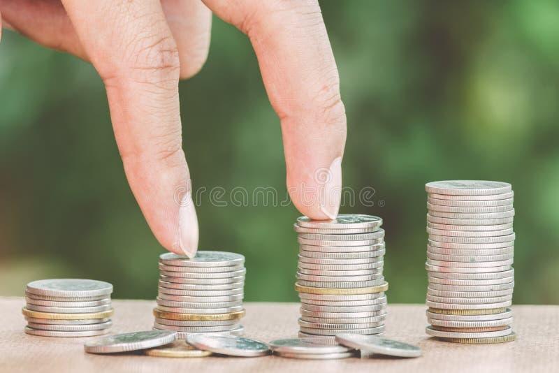 Mannelijke handstappen op geldmuntstuk zoals stapel groeiende zaken stock afbeeldingen