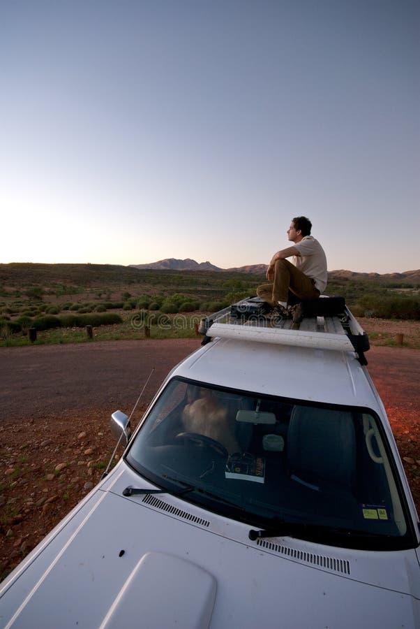 Mannelijke het Letten op Zonsondergang van dak van auto stock fotografie