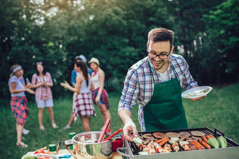 Mannelijke het voorbereidingen treffen barbecue in openlucht voor vrienden stock afbeeldingen