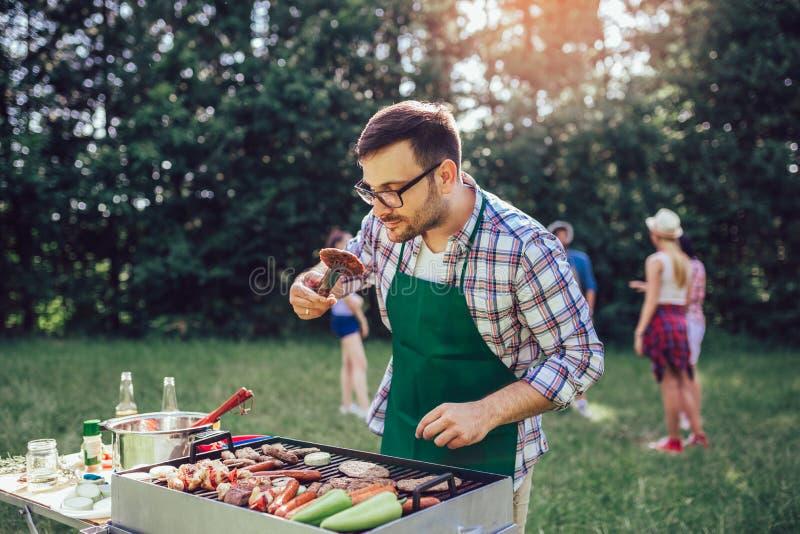 Mannelijke het voorbereidingen treffen barbecue in openlucht voor vrienden royalty-vrije stock foto's