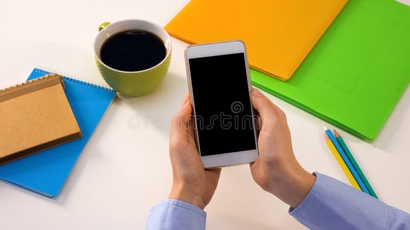 Mannelijke holdingssmartphone met het zwarte scherm in bureau, zaken app, malplaatje royalty-vrije stock foto's
